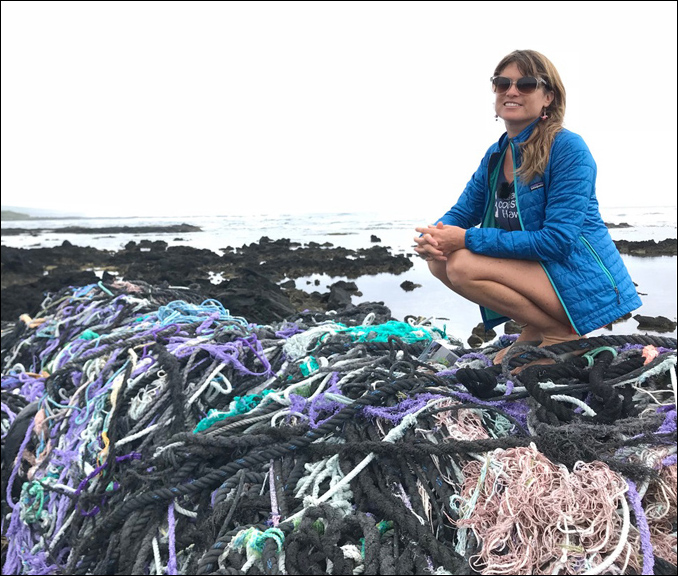 Sarah-Jeanne Royer perches on mound of nets washed ashore in Hawai'i.