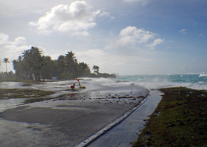 Waves wash over a flat coastal zone of Roi-Namur Atoll